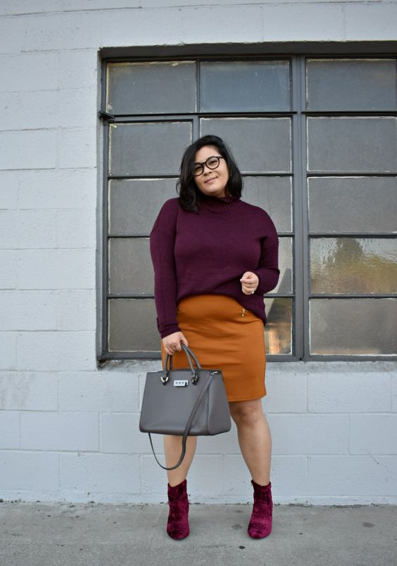 a mustard over the knee skirt, a plum-colored sweater, plum-colored boots and a grey bag