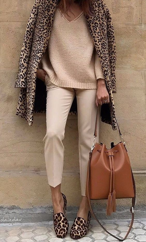a tan sweater, tan pants, a camel bag, leopard flats and a coat