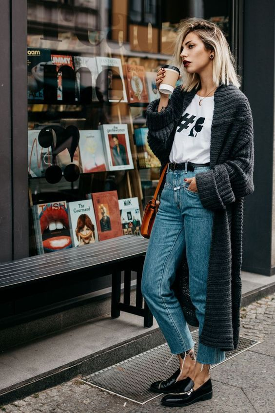 a weekend outfit with a logo t-shirt, blue cropped jeans, a chunky knit long cardigan and blakc flats
