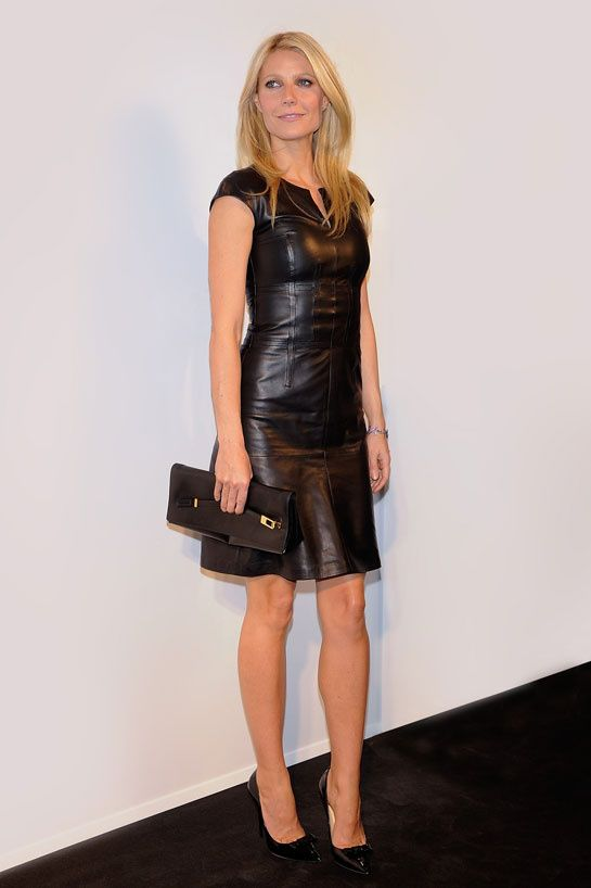 Gwyneth Paltrow weaing a black over the knee leather dress, black pumps and a clutch