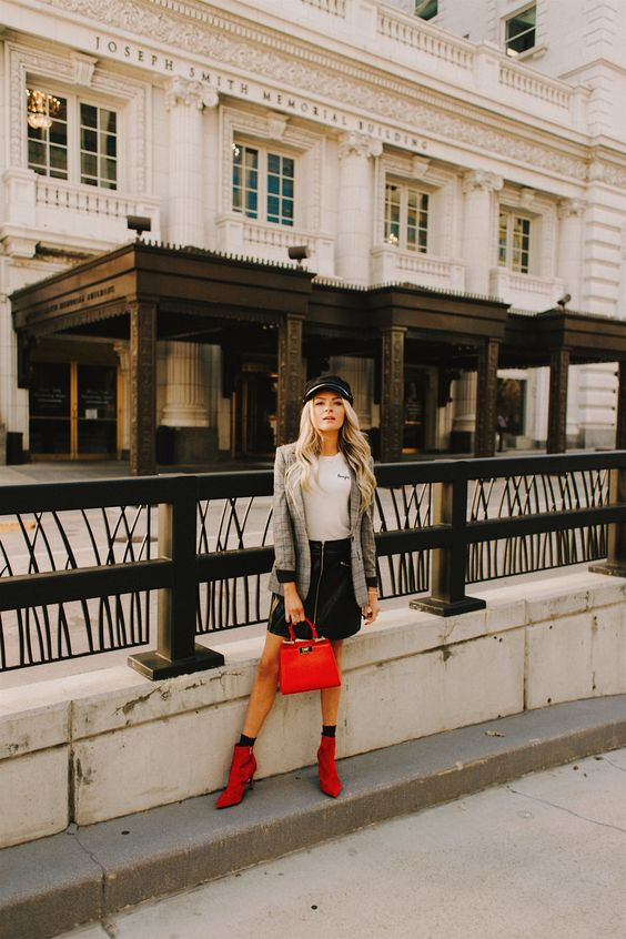 a black leather skirt, a white t-shirt, a tweed jacket, red boots and a black cabbie hat