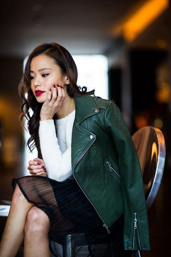 a green leather jacket, a white sweater, a black skirt with a sheer part and a red lip for a date