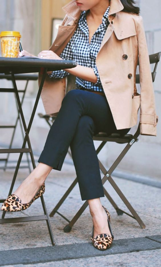 a preppy look with navy pants, a checked shirt, a tan trench and lopard moccasins