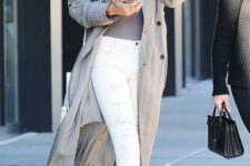 06 Gigi Hadid wearing white ripped skinnies, white heels, a grey top and a grey duster coat