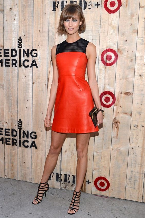 Karlie Kloss wearing a sheath red leather dress with a lace top and strappy heels