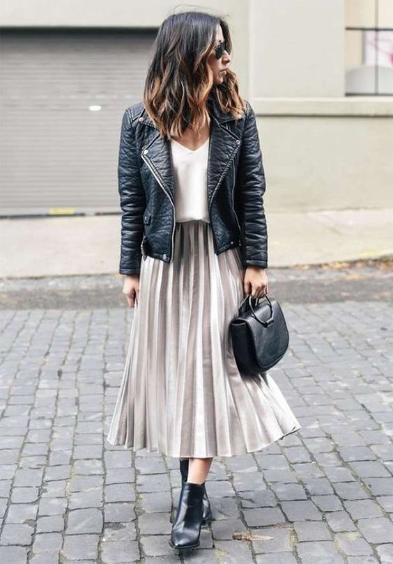 a white top, an off-white pleated skirt, a black leather jacket, black boots and a bag
