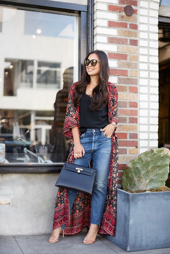 rough edge jeans, a black top, a fall-colored printed kimono and a black bag