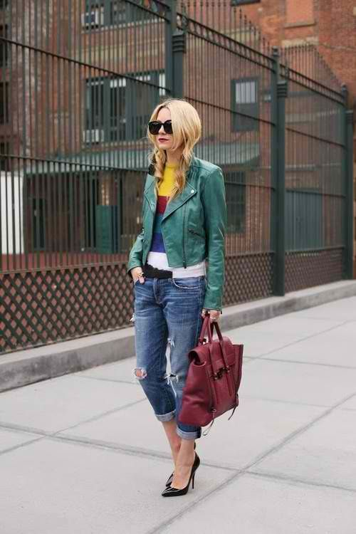 a colorful striped sweater, cropped blue jeans, heels, a burgundy leather bag and a grene leather jacket