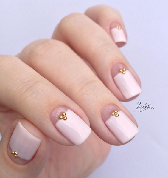 a girlish take on French nails with a large creamy tip and little rhinestones for a chic look