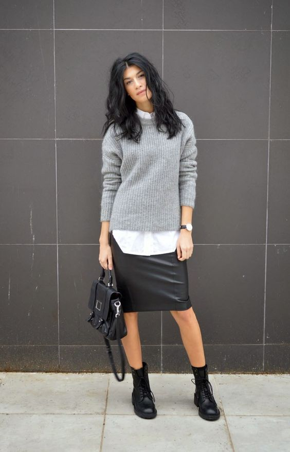 a white shirt, a grey sweater, a black leather skirt, black combat boots and a black bag for a casual look