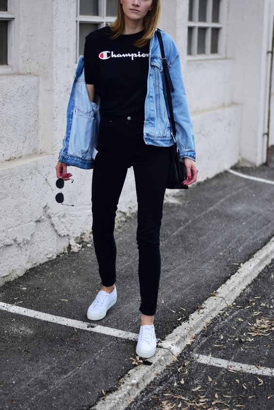 black jeans, a blakc logo tee, a blue denim jacket and white sneakers