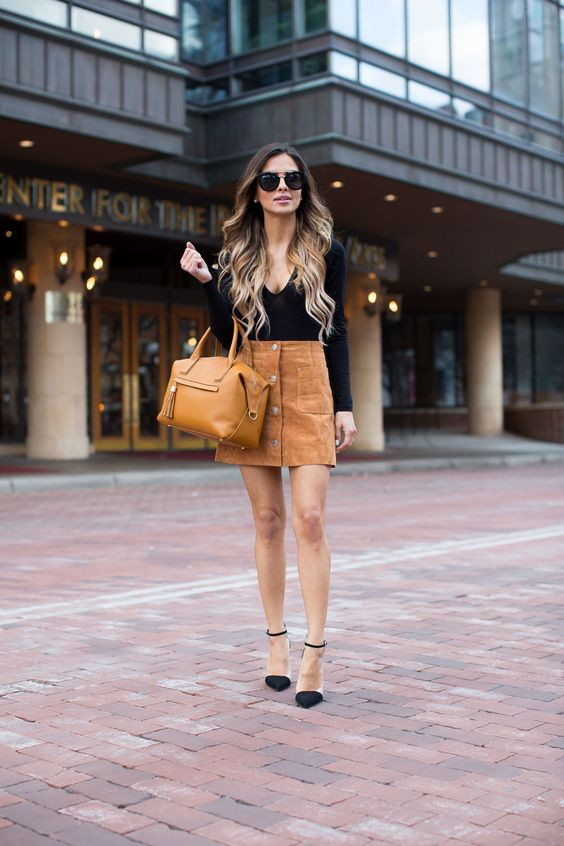 a black top with long sleeves, a rust high waist suede skirt with buttons and a mustard bag