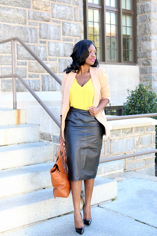 a bold yellow top, a black leather skirt, a tan blazerm a brown bag and black shoes
