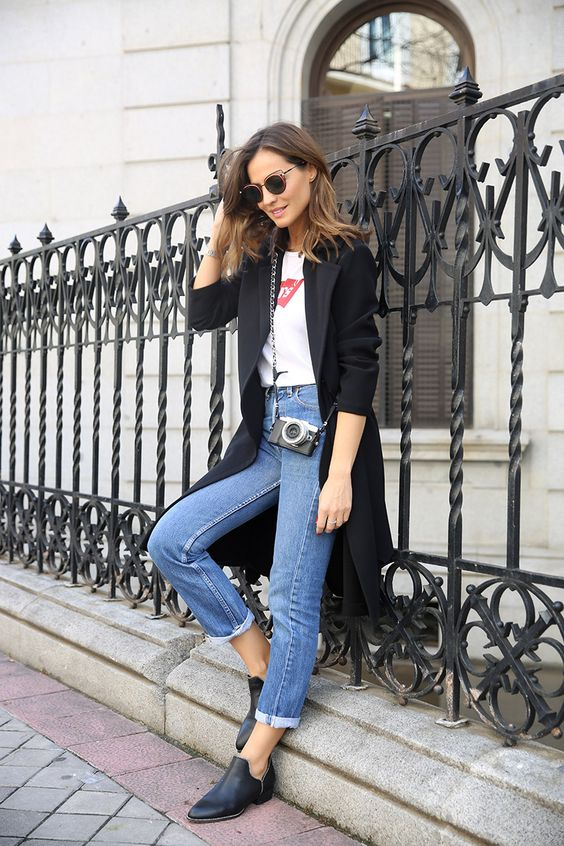 a white logo t-shirt, blue jeans, a black trench and black booties