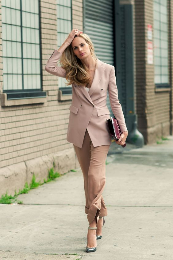 camel pants, a white top, a dusty pink blazer,  muted green shoes and a plum-colored clutch