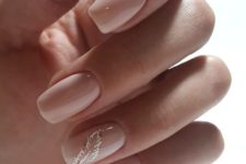 08 glossy nude nails with a white and glitter feather as an accent looks ethereal