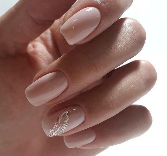 glossy nude nails with a white and glitter feather as an accent looks ethereal
