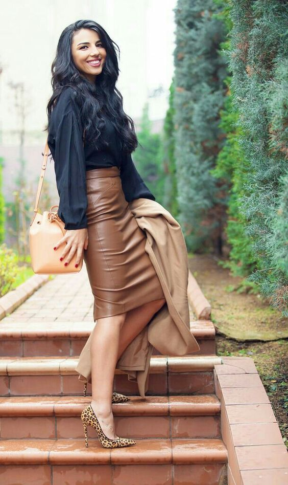 a black shirt, a brown pencil leather skirt, leopard shoes and a tan trench