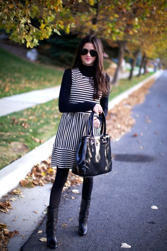 a striped sleeveless over the knee dress, a black top, tights and boots