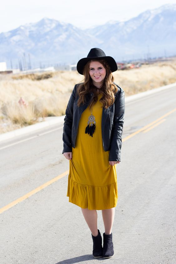 black boots, a mustard dress, a black leather jacket and a black hat
