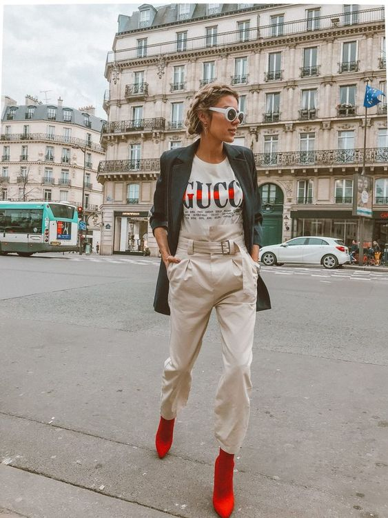 neutral high waisted pants, a logo tee, a black oversized jacket and red sock boots
