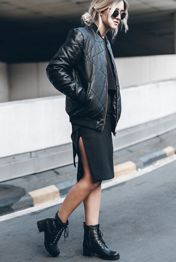 a black skirt with a slit, a black top, a black bomber jacket and combat boots