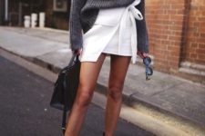 10 a chic look with a white wrap mini skirt, an oversized grey sweater, blakc strappy heels and a black bag