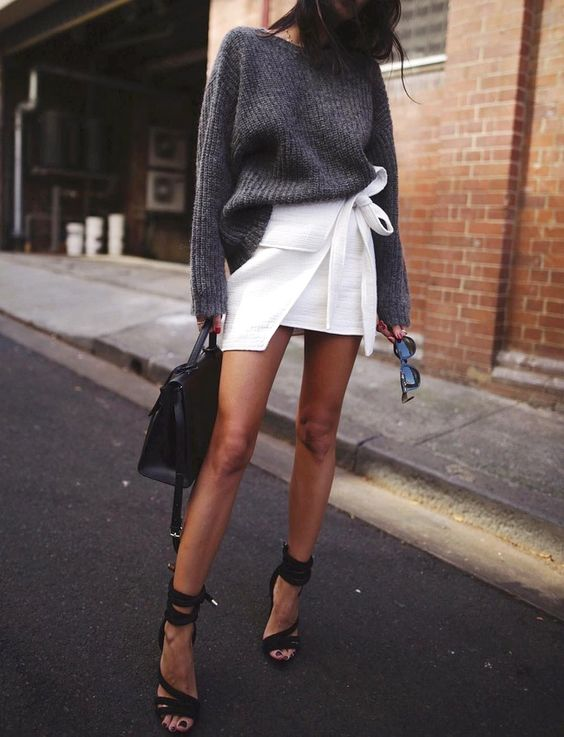 a chic look with a white wrap mini skirt, an oversized grey sweater, blakc strappy heels and a black bag