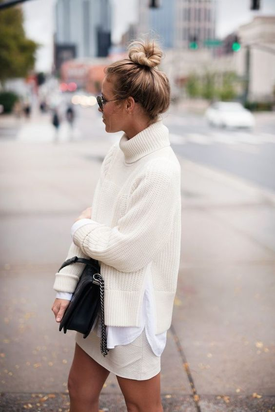 a creamy sweater, a white shirt, a creamy skirt plus a black bag