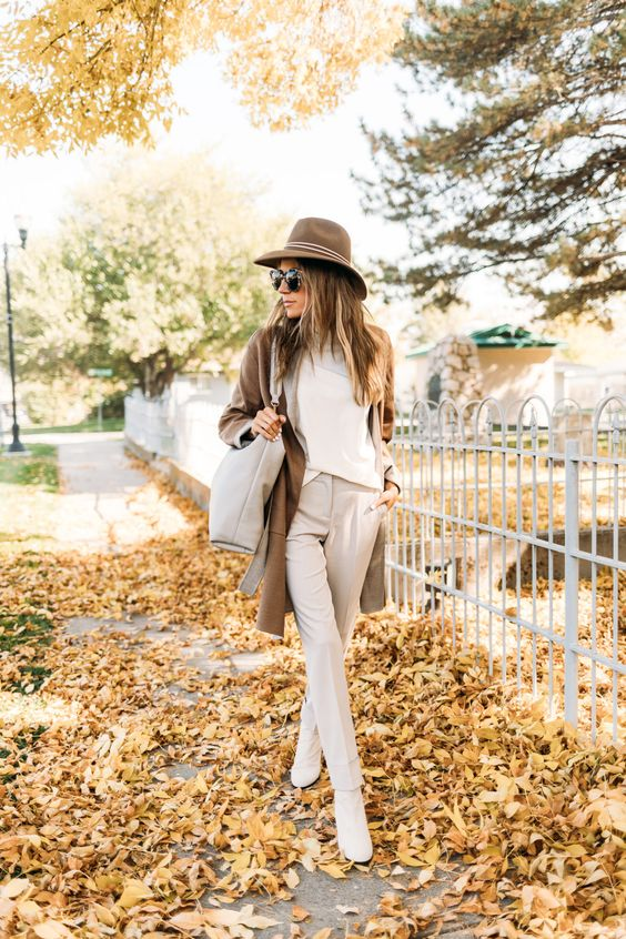 a creamy top, pants and booties, a camel cardigan, a brown hat and a creamy bag