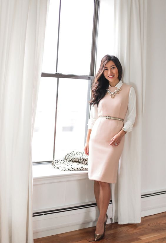 a pink sleeveless knee dress styled with a white shirt, a statement necklace and heels