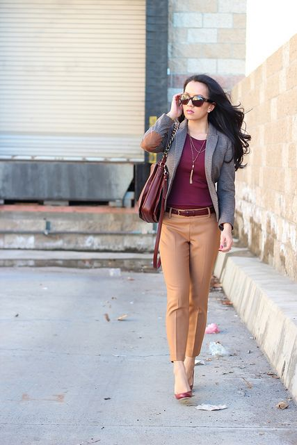 a plum-colored top, tan-colored pants, plum-colored shoes and a grey blazer