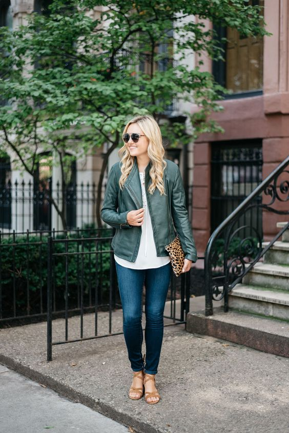 a white shirt, a grene leather jacket, blue denim and strappy brown shoes