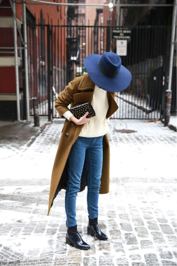 black boots, blue denim, a creamy sweater, a brown coat and a navy hat