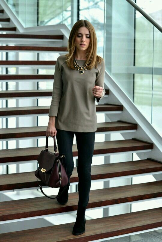 black pants, an olive green top, a plum-colored bag and a statement necklace