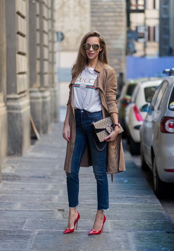 blue denim, a logo t-shirt, a tan trench, red shoes and a bag