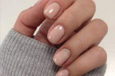 10 nude nails spruced up with a statement nail with gold beads at the cuticle