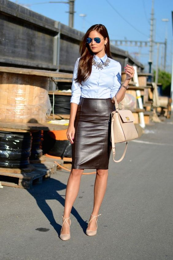 a blue shirt, a statement necklace, a brown leather skirt, nude shoes and a matching bag