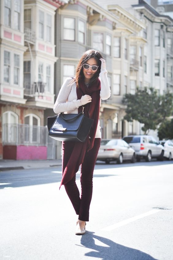 a simple combo of a white top, plum-colored pants and a scarf and a black bag
