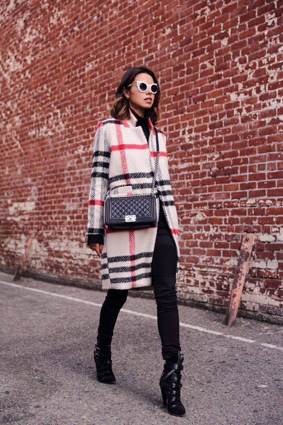 a total black look spruced up with a plaid coat as a touch of color