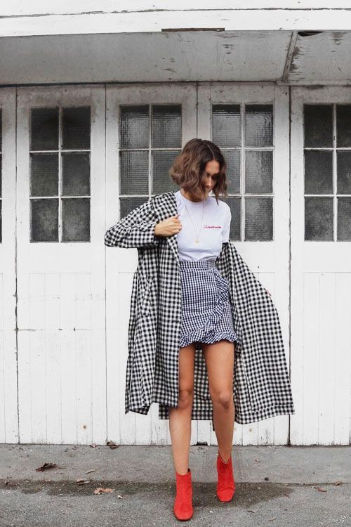 a white logo tee, a checked ruffle wrap skirt, a checked coat and red sock boots