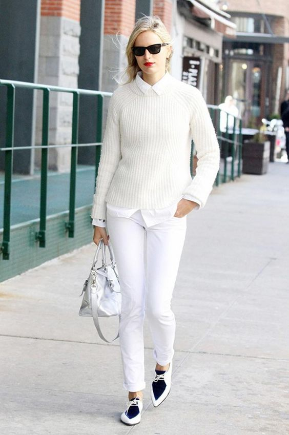 a white shirt and pants, a creamy sweater, a white bag and white and navy shoes
