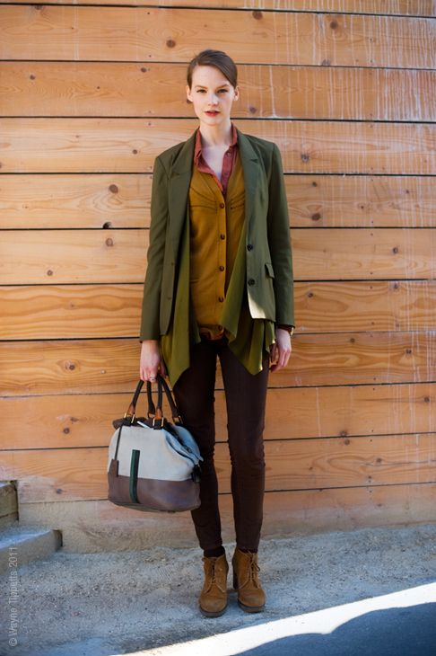 brown pants, a mustard cardigan, a coral shirt, a muted green blazer and brown boots