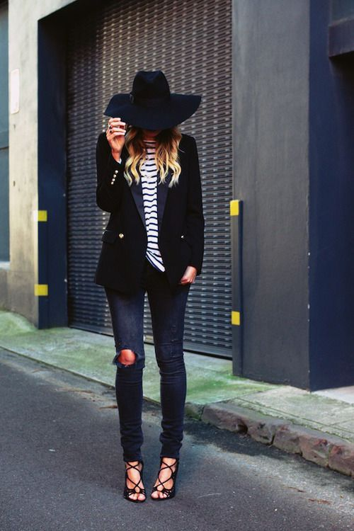 navy ripped jeans, black strappy heels a striped top, a black blazer and a fedora hat