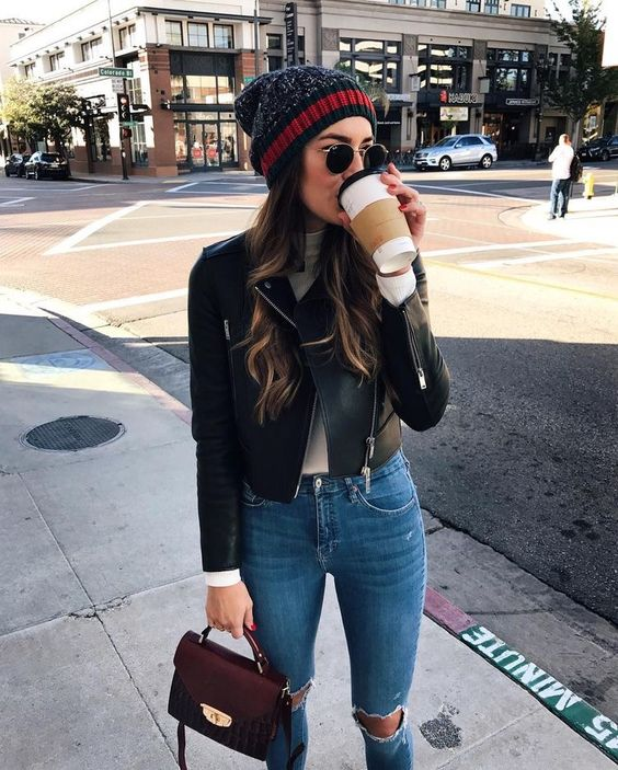 a casual look with ripped deim, a white turtleneck, a black leather jacket, a beanie and a small bag