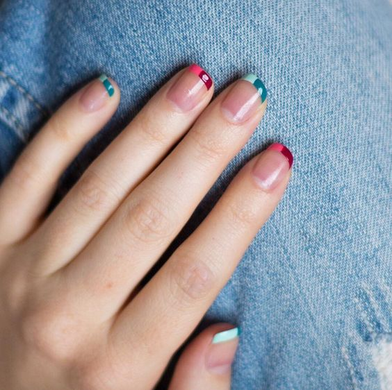 a colorful and mismatching French manicure with green and pink tips