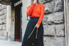 12 a navy pleated midi skirt, an orange patterned sweater, two toned shoes and a black bag