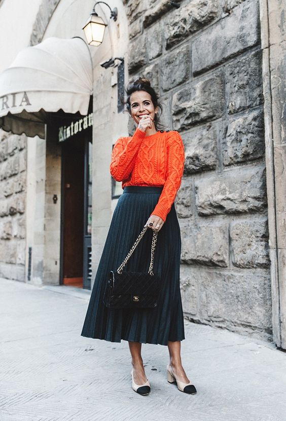 a navy pleated midi skirt, an orange patterned sweater, two toned shoes and a black bag