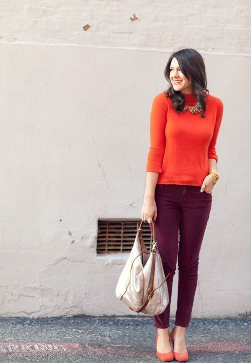 an orange turtleneck, plum-colored pants, orange shoes and a neutral bag