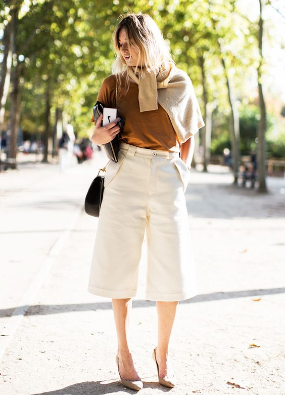 grey heels, a mustard top, a beige sweater, creamy culottes for a bright touch